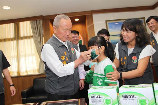 苗栗縣政府16日獲熱心企業捐贈30.5萬片醫療口罩,由苗栗縣長徐耀昌代表收下,並為孩童戴上口罩,為防疫超前部屬。(何冠嫻攝)