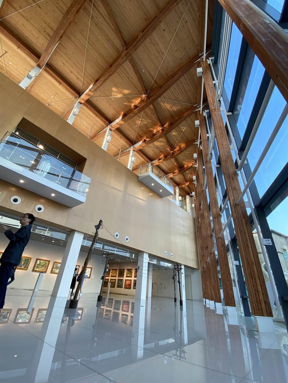 到嘉義美術館二樓,可以看到挑高的木構建築設計及大片的落地玻璃,大廳空間採用集成材樑柱而非鋼構,呼應嘉義作為「木都」的歷史特色。(馮惠宜攝)
