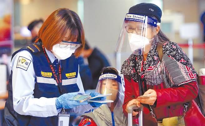 衛福部開設「新冠疫苗臨床試驗意向登記平台」爭議不斷,一旦受試者有不良反應,恐無法申請國賠。圖為在桃園機場入境管制區內,1名防疫人員正在查驗旅客的健康聲明書。(本報資料照片)