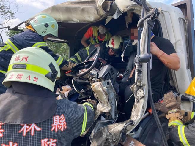 驾驶大货车的45岁庄姓男子被撞毁的底座夹住动弹不得,横杆穿刺他的右膝,云林县消防局人员费力抢救。(云林县消防局提供)