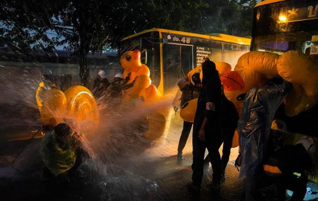 泰国警方动用水炮驱逐群眾,而群眾则用充气游泳浮具当盾牌。(图/路透社)
