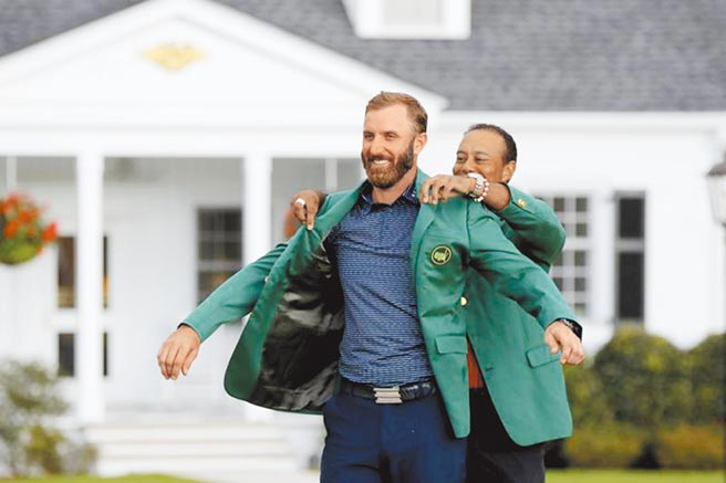 世界球王強生(前)以破紀錄的-20桿奪下名人賽冠軍,衛冕失敗的老虎伍茲(後)為他穿上綠夾克。(美聯社)