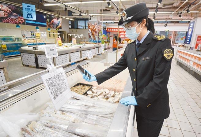 11月3日,北京市豐台區市場監督管理局東高地街道市場監管所的執法人員,核查超市內的進口冷凍食品追溯資訊。(新華社)