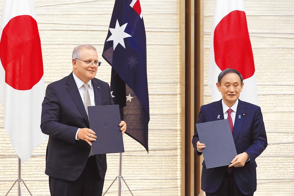 日本首相菅義偉(右)17日與來訪的澳洲總理莫里森簽署雙邊防衛協定。(美聯社)