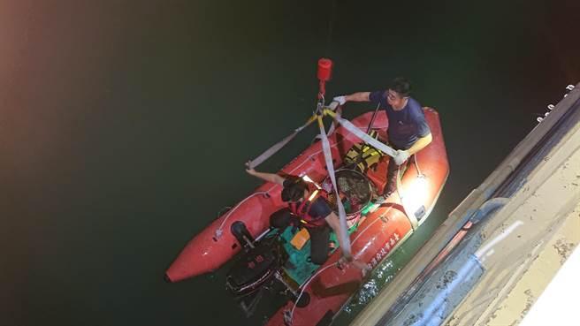 消防員搭配動保人員以橡皮汽艇打撈起溺斃的小黃狗。(程炳璋攝)
