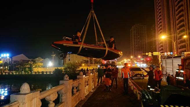 消防車吊掛橡皮汽艇下水救狗,不少民眾在岸邊等待,希望小狗能存活。(程炳璋攝)