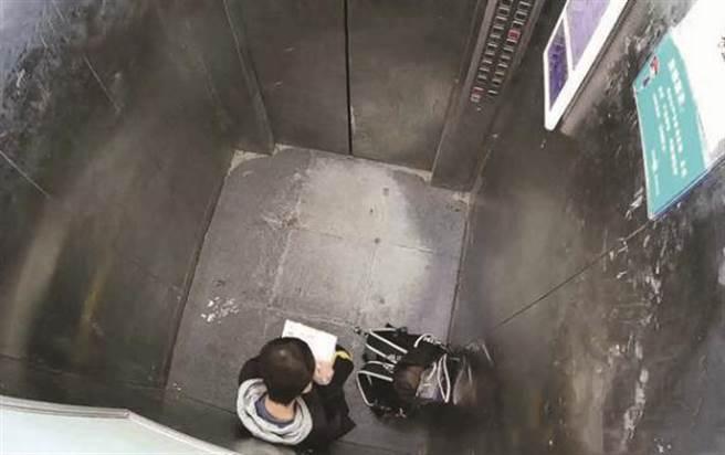 在等待救援的時間,趙姓男童竟默默地從書包內拿出作業,蹲坐在角落寫功課。(翻攝自人民網)