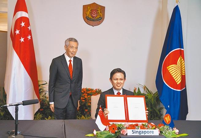 新加坡總理李顯龍表示,沒有多少國家願意加入「沒有中國的聯盟」。圖為15日李顯龍見證星國貿工部長陳振聲透過視訊方式簽署RCEP。(新加坡通訊及新聞部提供)