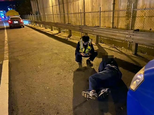 周姓男子行經桃園市八德區時,開車突然抽筋倒在路邊,警方連忙上前關心。(警方提供/賴佑維桃園傳真)