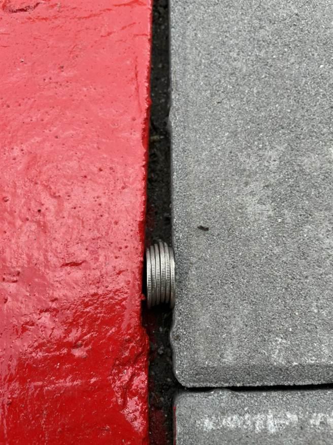 北市內湖大湖社區入口人行道日前才更新完成,但議員李明賢卻發現,地板的裂縫居然可放入6個銅板。(李明賢提供/張穎齊台北傳真)