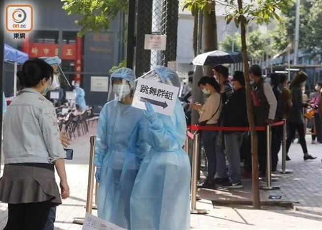 香港檢測社區中心外有工作人員指示「跳舞群組」排隊方向,現場大排長龍。(取自東網)