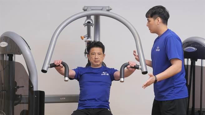 為提倡同仁在防疫期間保持良好運動習慣,由全球人壽健身指導員呂哲宇指導、法遵長林鼎鈞示範正確使用重量訓練器材的方式。(圖/全球人壽提供)