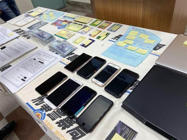 警方起出詐騙集團的筆電、行動電話、隨身碟、銀行存摺、銀行提款卡、U盾、教戰手冊及142萬元等贓證物。(盧金足攝)