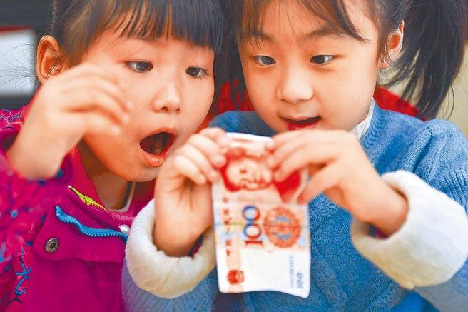 人民幣做為儲備貨幣的前景可能大大增強。圖為小朋友仔細分辨人民幣真偽。(中新社資料照片)