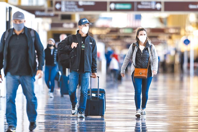 美國疫情嚴峻,民眾感恩節照常出行,11月24日,戴口罩的旅客走過機場通道。 (新華社)
