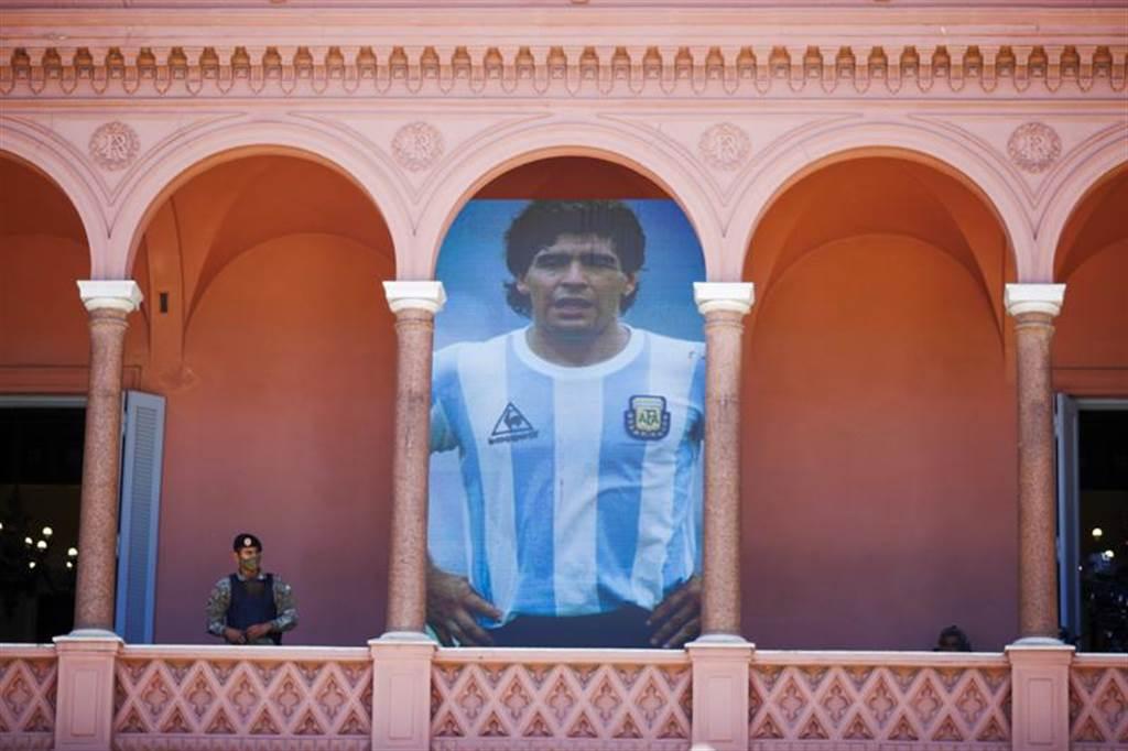 阿根廷首都布宜諾斯艾利市中心總統府玫瑰宮舉行馬拉度納悼念活動,數十萬人前往致意,總統府也公告全國進入3天哀悼期,以紀念這位偉大球星與國家英雄。圖為阿根廷總統府掛出印有馬拉度納照片的大型布幅。(圖/美聯社)