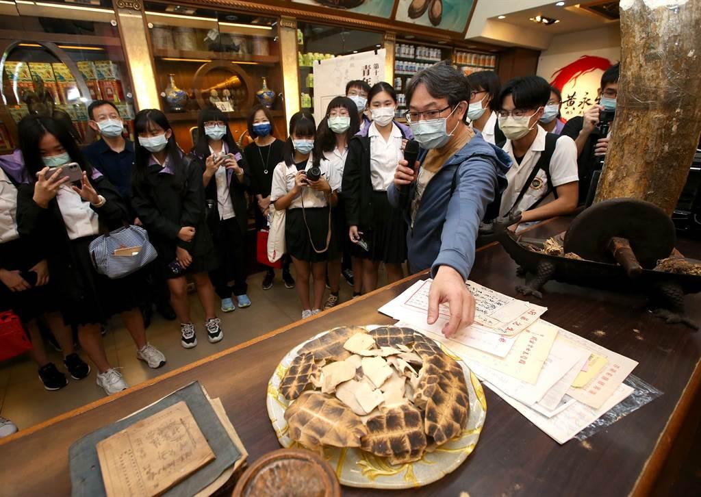 漢字藝術家古耀華27日與成淵高中學生來到迪化街走讀,逛老商行尋找漢字,在黃永生蔘藥行解釋龜板與發現甲骨文的歷史。(趙雙傑攝)