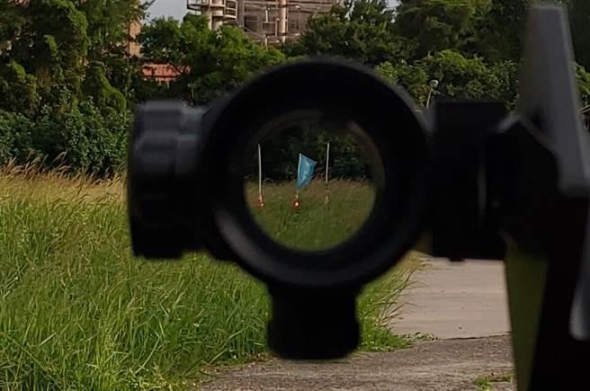透過瞄準鏡所看見之影像,旗座下方為瞄準用紅色光點。(姜霏翻攝)