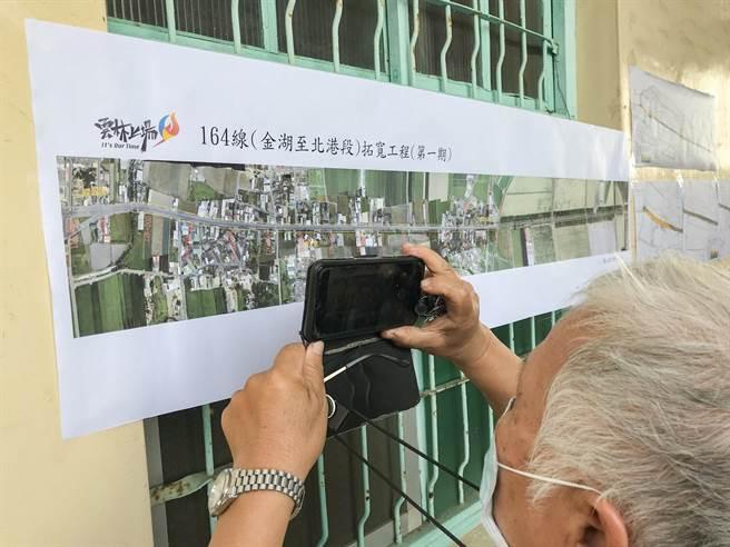 七旬老翁拿起手機拍照,確認自家土地是否在徵收範圍內,村民擔憂雲164縣道拓寬工程將損害居住權益。(周書聖攝)
