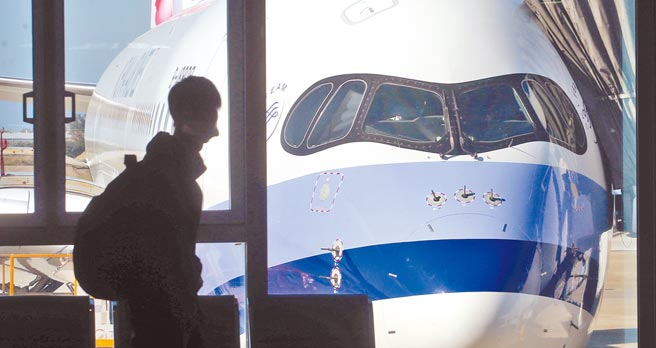 受新冠肺炎疫情影響,許多在國外就學的台灣籍學生紛紛返台就學,其中不乏名校學生。在桃園機場入境管制區內,1名旅客走過候機室的落地窗前。(范揚光攝)