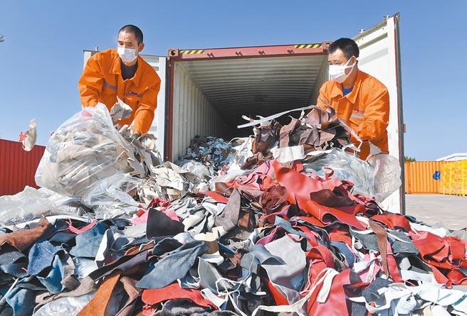 大陸明年起禁止進口固體廢物,對洋垃圾說不。圖為工人在廈門海關清理查獲的進口洋垃圾。(新華社)