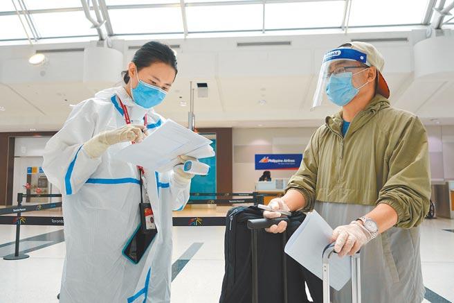 航空人員對準備搭乘航班的乘客查驗新冠病毒核酸檢測陰性證明。(中新社資料照片)