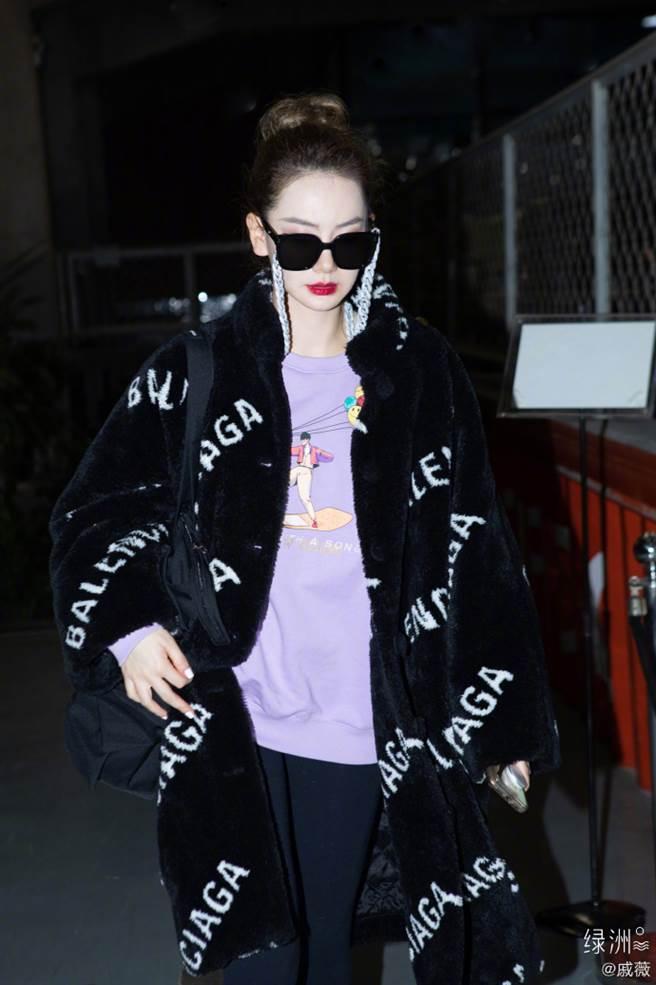 這套黑色絨毛大衣給人一種高級名媛感,加上白色LOGO字體,形成撞色的視覺效果。(圖/摘自微博@戚薇)