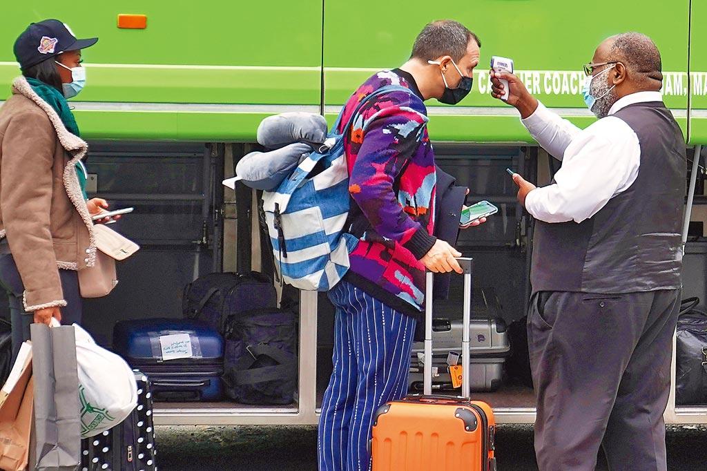 紐約市曼哈頓區,一名巴士司機正在為上車的旅遊量體溫。感恩節期間,美國有數以百萬計民眾搭乘公共交通工具返家過節。(路透)