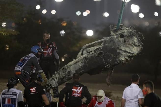 賽車斷成兩截,前半截撞穿護欄起火燒毀。(美聯社)