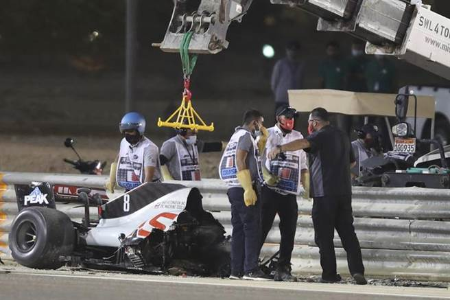 賽車斷成兩截,後半截還留在護欄外,工作人員吊掛移走。(美聯社)