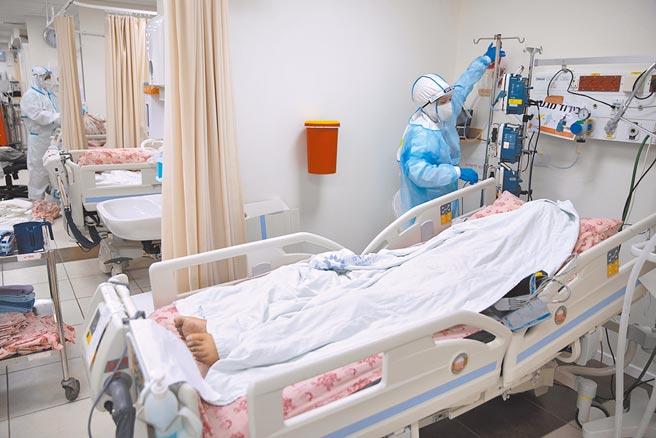 新冠病毒造成全球6200萬人確診,近150萬人死亡。美國紐約至今仍有至少650具屍體放在冷藏車中,原因是沒有家屬認領。圖為醫護人員為整理醫療設備,病床上是因新冠病毒過世病人。(美聯社)