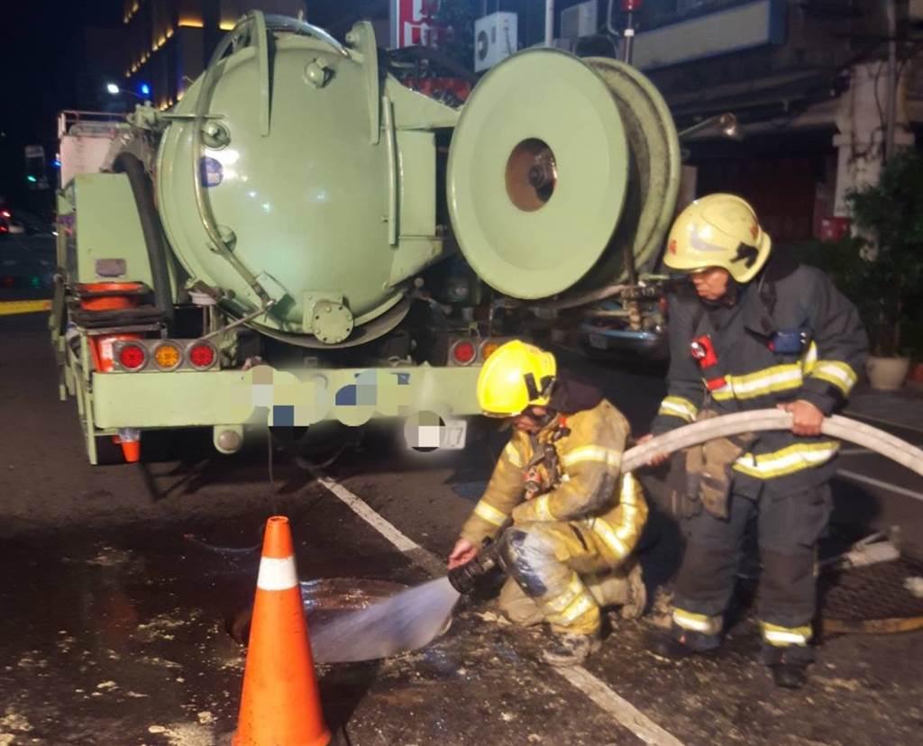 高雄市驚傳下水道沼氣奪命,消防人員到場使用儀器測得沼氣,以灑水方式降低沼氣濃度。(高市消防局提供/袁庭堯高雄傳真)