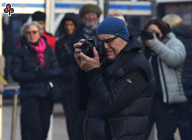 《環時》社評批與澳洲掰扯善惡很累也不值。圖為去年12月9日澳洲遊客在新疆喀什古城景區內遊玩拍照。(新華社)