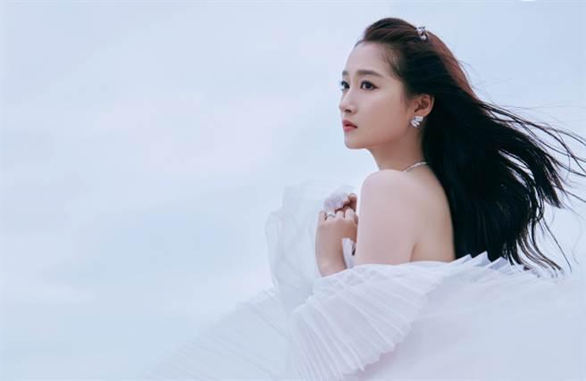 關曉彤穿上一套珍珠白浪花裙前往海邊拍攝一系列寫真。(圖/摘自微博@关晓彤工作室)