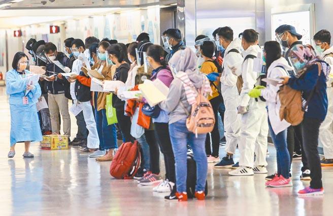 印尼移工新冠肺炎移入個案暴增,中央流行疫情指揮中心昨日宣布12月4日起暫停引進印尼籍移工2周。圖為昨晚來台的62名印尼移工,在勞動部委外工作人員引導下,準備辦理入境手續。(陳麒全攝)