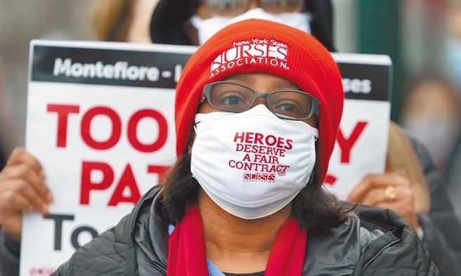 美國29日染疫住院人數已超過9萬3000人,再創新高。圖為一名正在罷工的護士。(美聯社)