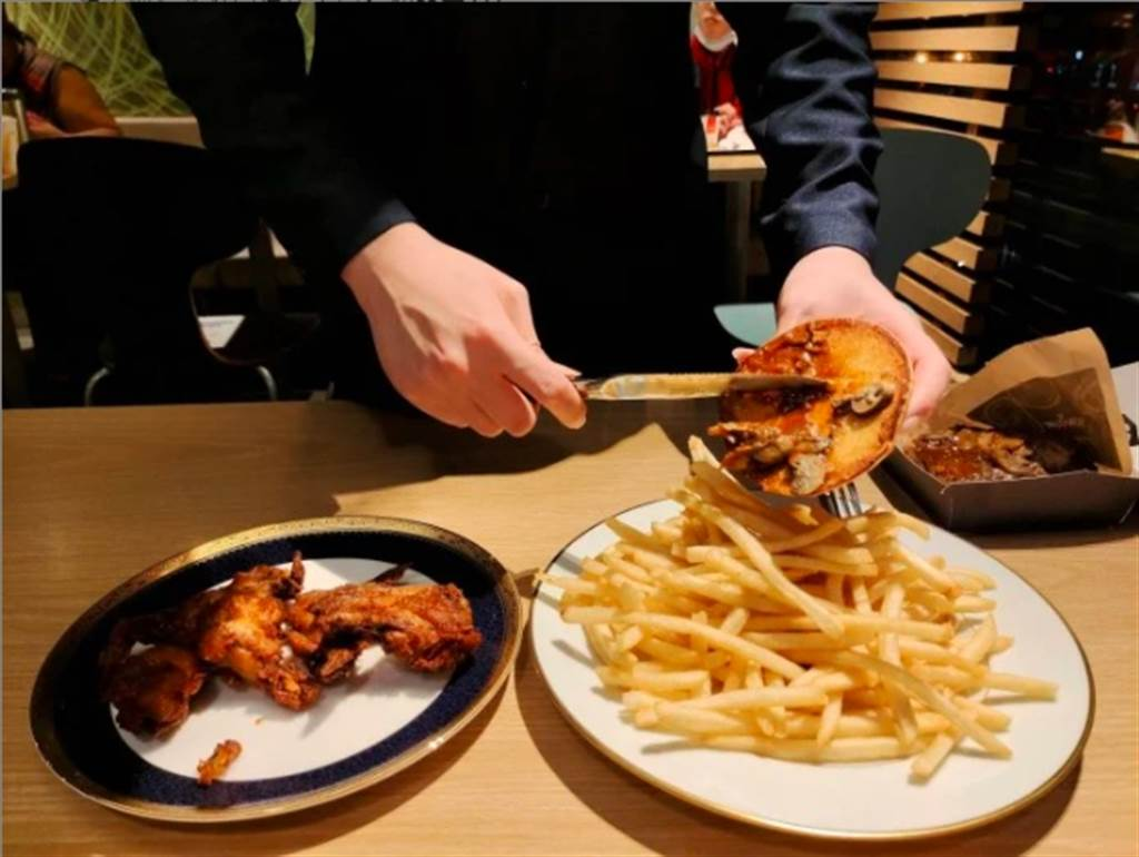 男友不慌不忙地拿出包包裡的盤子跟刀叉,點餐完後,開始將漢堡裡的松露醬挖出,並倒在雞翅、薯條上。(摘自Dcard)