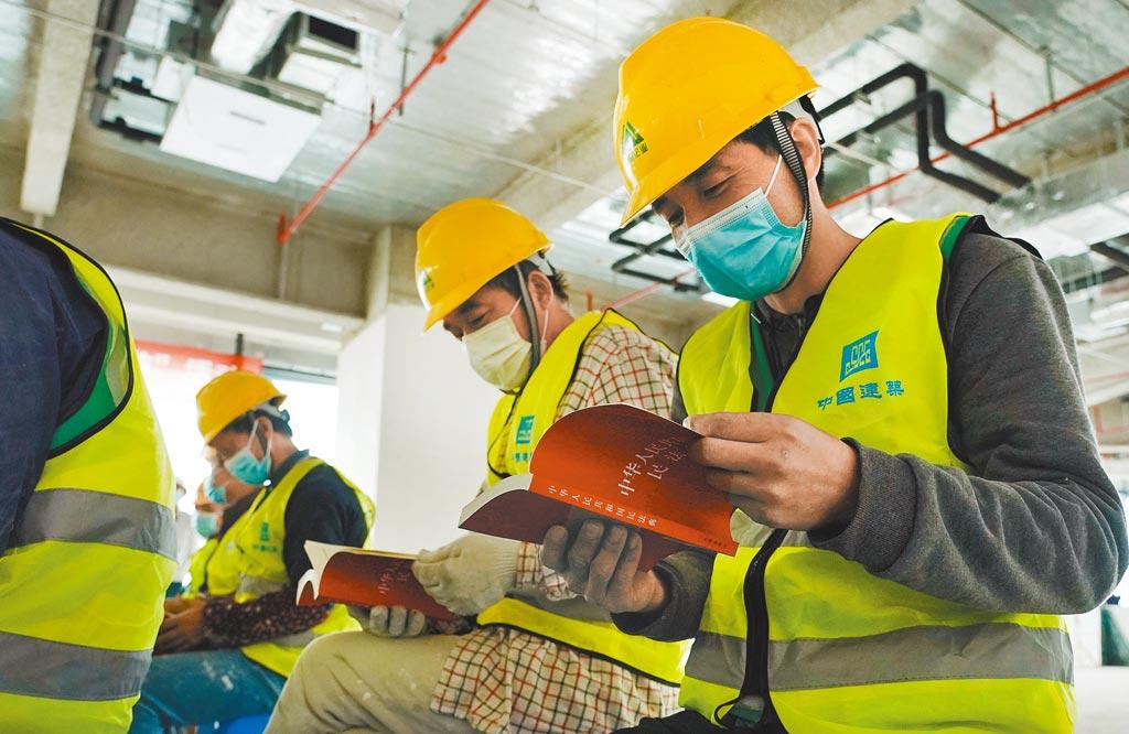 建築工人翻閱大陸《民法典》。(新華社資料照片)