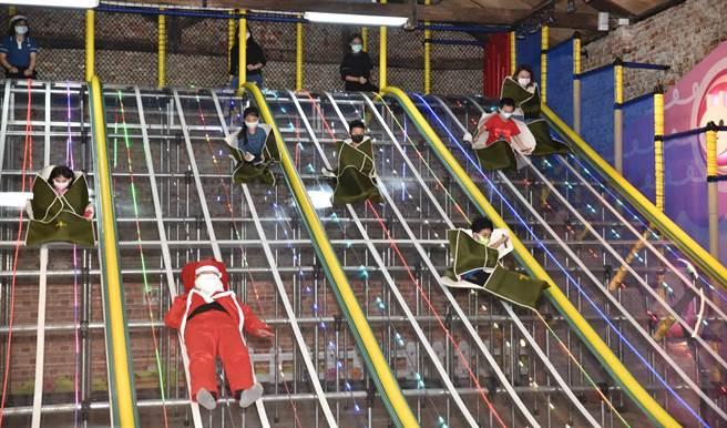 高雄十鼓橋頭文創園區工作人員扮成耶誕老人,與孩子們一起玩瀑布滑梯。(林瑞益攝)