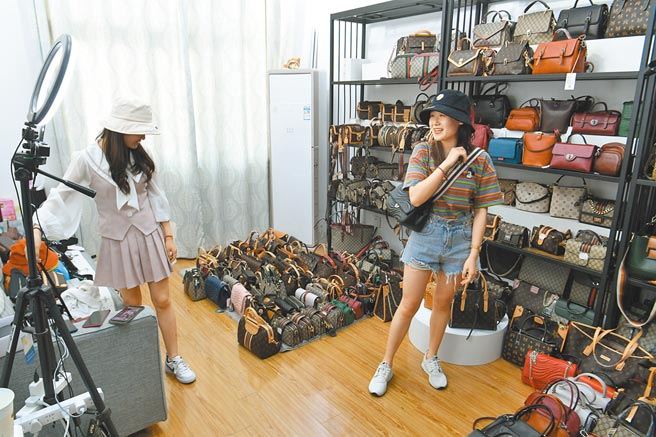 5月11日,在安徽合肥白馬萬商服裝城,主播在店舖內通過線上直播銷售商品。(中新社)
