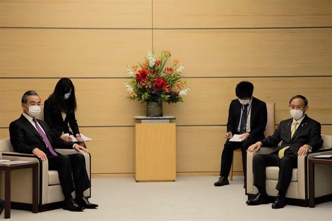 日本首相菅义伟(右)接见中国外交部长王毅(左)。(中新社资料照片)