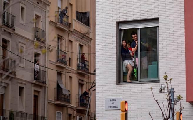 因新冠肺炎疫情封城期間,窗邊、陽台是民眾能稍微喘口氣的地方。圖為西班牙巴塞隆納居民站在窗邊、陽台。(圖/美聯社)
