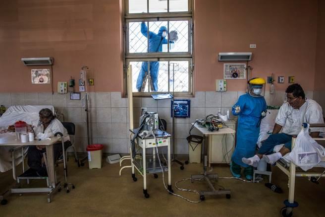不只醫護人員,就連刷洗加護病房外窗戶的清潔工人也得穿戴全套防護服。(圖/美聯社)