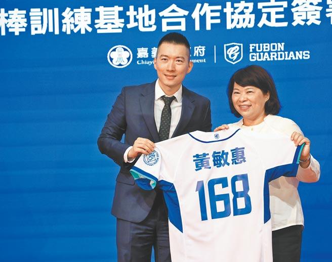 富邦悍將領隊蔡承儒(左)與嘉義市長黃敏惠(右)簽署職棒訓練基地合作協定,贈與一件球衣。(富邦悍將提供)