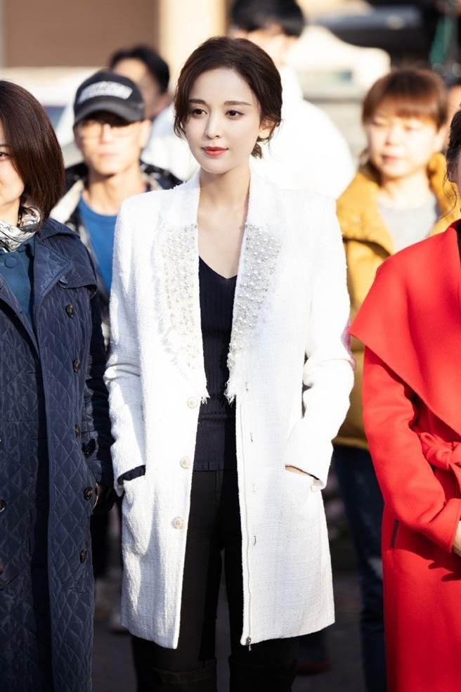 娜扎穿上小香風白色長版大衣,內搭一件黑色低領口的毛衣及深色緊身褲,以黑白撞色搭法穿出經典的簡約風格。(圖/摘自微博@娜扎工作室)