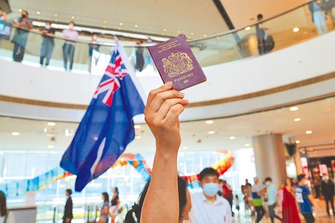 今年5月,在香港一處購物中心,示威者拿著一本英國護照並舉起一面英屬時期的香港旗。《香港國安法》通過之後,英國大量核發英國護照給香港居民,以表達對港人的支持。(美聯社)