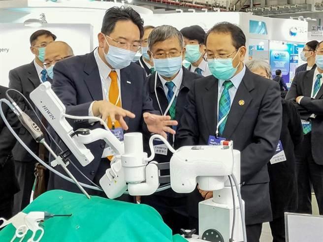 在馬偕醫院出生的上銀科技董事長卓文恒(左一)在台灣醫療科技展,向馬偕醫院胡志彊董事長(右一)解說上銀自行開發的內視鏡扶持機器手臂。(圖/上銀提供)
