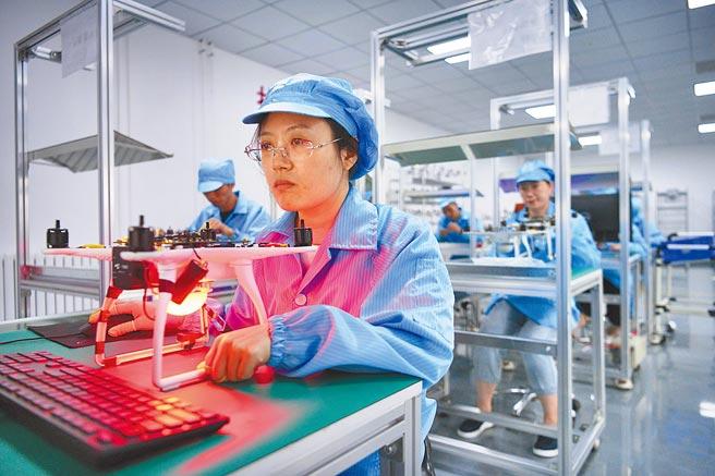 天津一科技廠,高級電子裝調工對一架無人機焊接積體電路板進行檢測。(中新社資料照片)