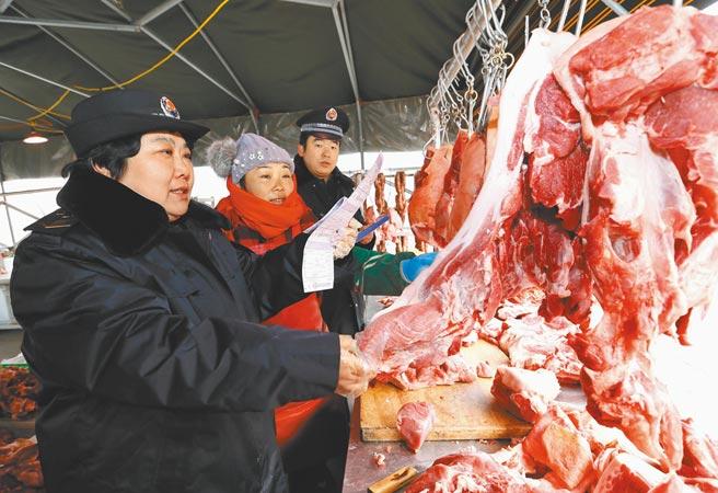 山東青島食品藥品監督管理局工作人員在一家農貿市場對肉類食品進行抽查。(新華社資料照片)