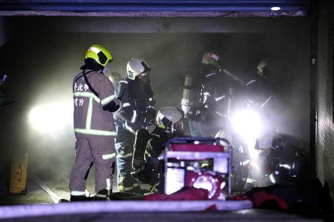 消防隊員在車道入口處整裝,準備進入地下停車場救災。(黃世麒攝)
